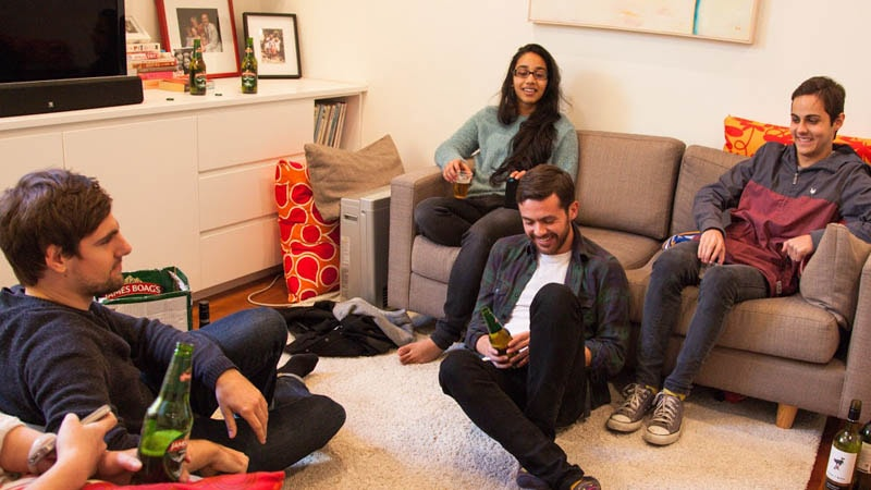 Group of four friends hanging with beer in lounge room