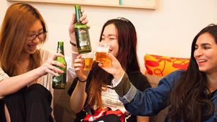 Group of three girls doing a toast with beer