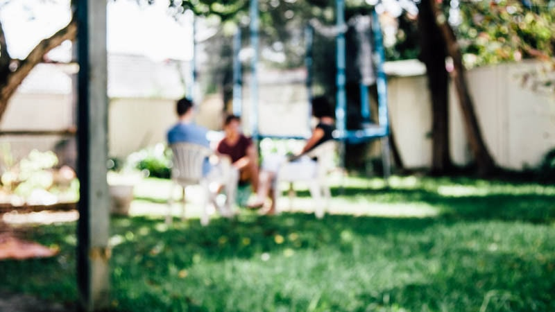 parent sitting with children in backyard