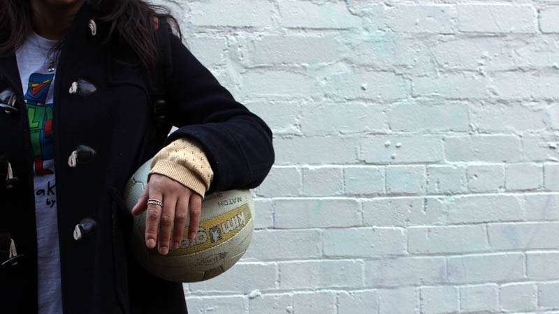 Girl standing against white wall with netball