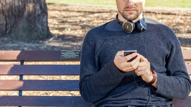 Close up of guy sitting on park bench using his phone