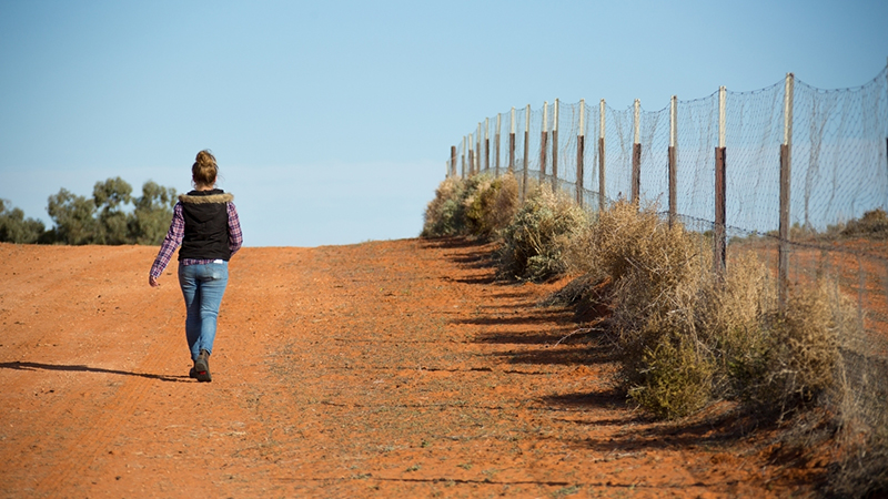 a woman walking on red earth next to a fence