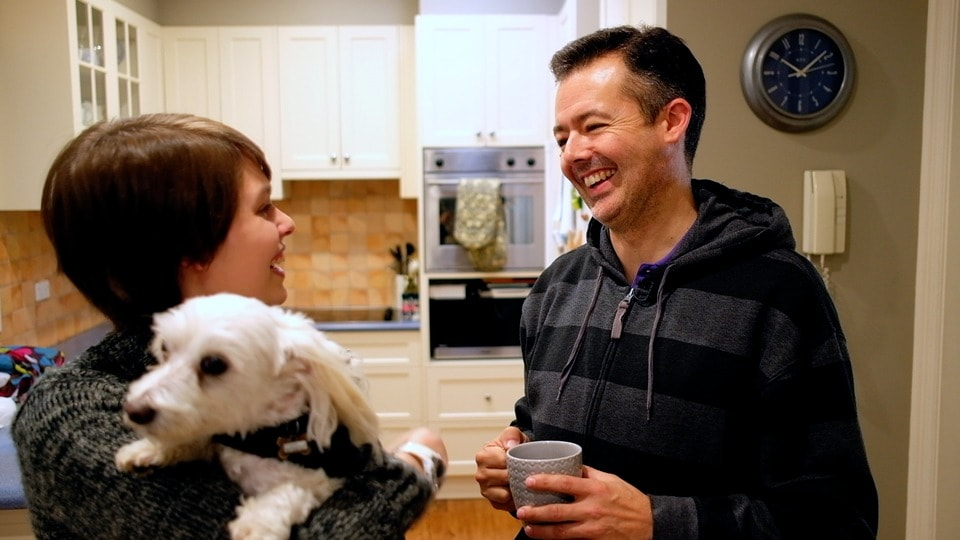 father smiles at daughter whilst she looks at him and holds their dog