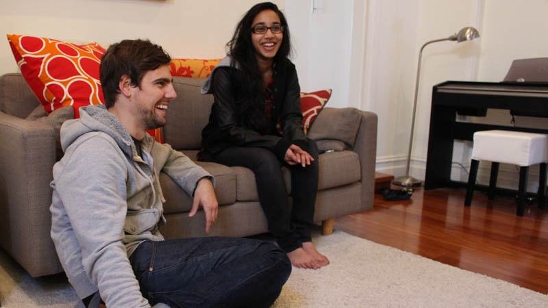 Guy and girl sitting on couch laughing