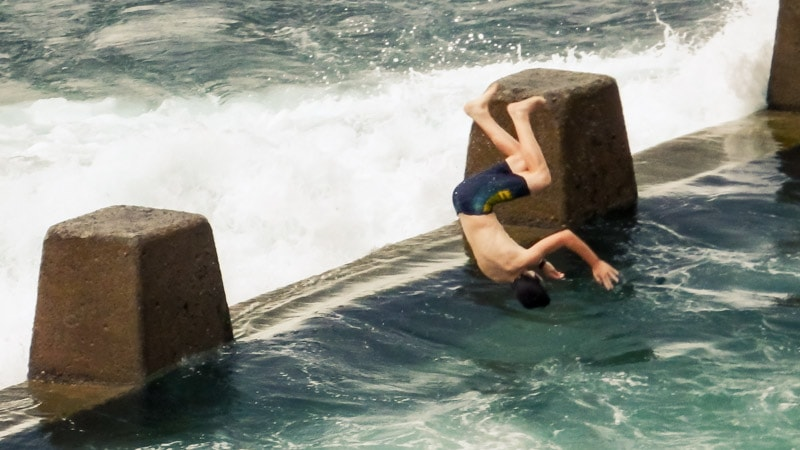 boy jumping into rock pool