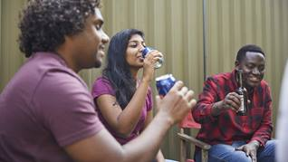 three young people drinking alcohol