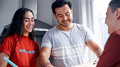 teenage girl smiling with dad and another teenager in kitchen