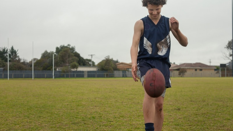 boy playing AFL on an oval