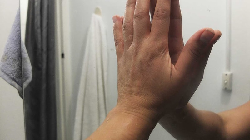 Person hand on bathroom mirror