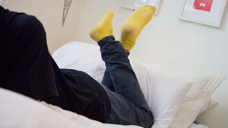Yellow socks on person lying on bed with legs crossed