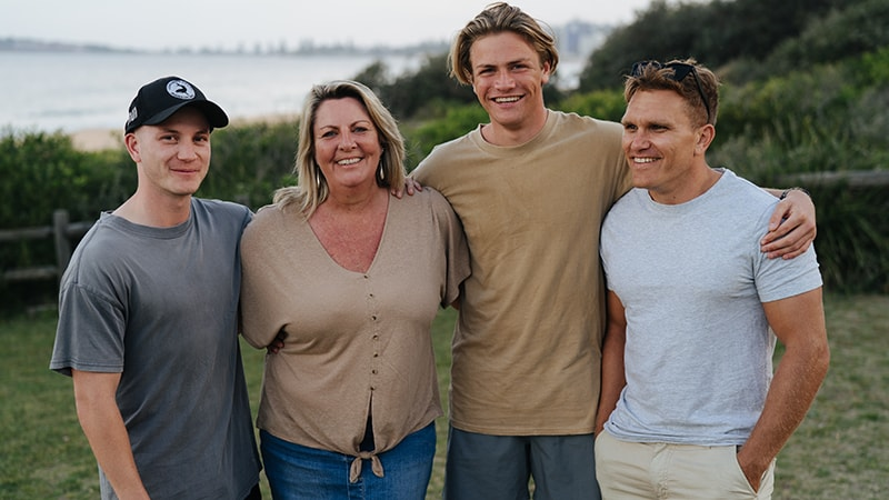 mother son and two friends smiling with arms around each other