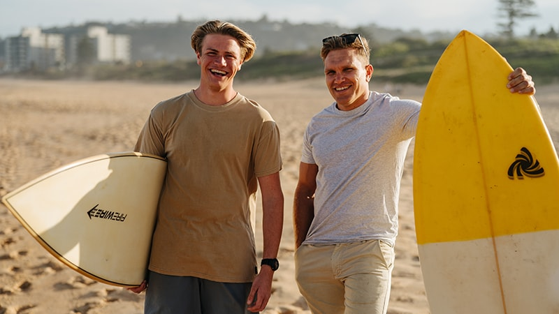 teenage boy and young man standing on beach with surfboards
